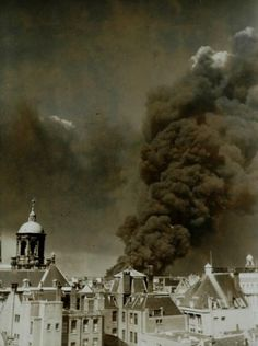Tweede Wereldoorlog. Brandende olietank van Shell, gezien vanuit de stad. Grote zwarte rookwolken boven Amsterdam, mei 1940. LET OP! Dit is een minimaal bewerkt lowres bestand. Wilt u een groter en/of bewerkt bestand neem dan contact op met 070-3314160 of verkoop@spaarnestadphoto.nl.