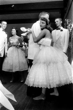 A high school girl dances barefoot at her prom, 1950s.