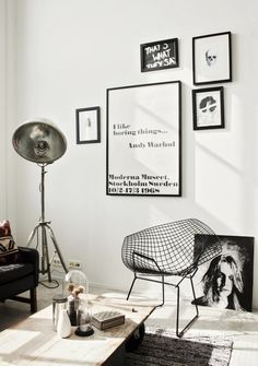 Minimalist living space with text-heavy artworks, a production light, and a modern metal chair