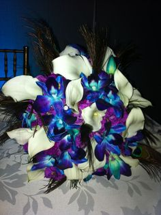 Peacock Bridal bouquet- Blue bomb dendrobium orchids, calla lilies, and purple stock with peacock feathers