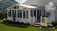 All Season Sunroom with white vinyl frame with gable roof and side deck by Patio Enclosures.