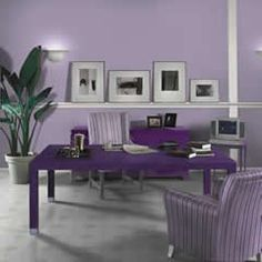 Purple office. Lavendar walls, white office chair, deep purple chairs for guests