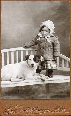 Vintage photo, little girl wearing bonnet and dog on bench.