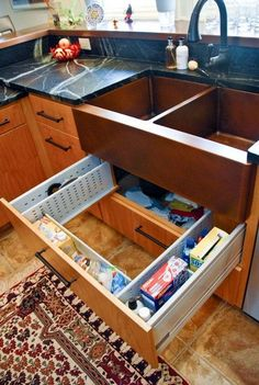 Sink Drawer Surround Plumbing. The sink drawer is adjustable to fit around the plumbing and disposal below. It's a great spot for all the sponges, dish soap, trash bags and cleaning supplies that usually get lost in the dark corners. http://hative.com/creative-under-sink-storage-ideas/