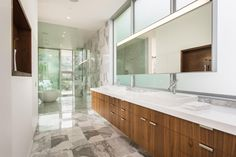 This elegant, master en suite brings some of the elements of the kitchen, such as the zebra wood cabinets and white countertops, and blends them with the gray and white tile to give the whole house continuity.