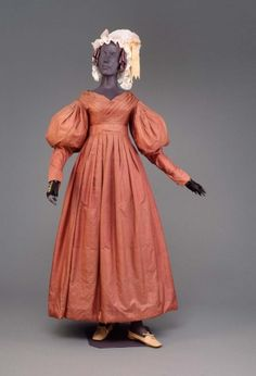 A cotton glazed gown from the Romantic Period in the 1830's. It is a simple gown, dyed a rust orange color for a nature look. Has the infamous drooped puffed sleeves at the biceps and a very high waistline.