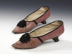 Shoes, Great Britain, 1780-1800, Silk, kid, tanning and stencillling. Made of pink kid, they are stencilled with an all-over triangular design in black, and bound with black ribbed silk tape. The shape of the long pointed toes is mirrored in the throat, further emphasised by a black pom-pom at the center front. The heels are covered in dark brown leather.