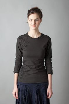 """This 100% medium-weight organic cotton jersey fitted T-shirt features our Magdalena stencil, sewn in placement fashion using reverse appliqué. Measures 26"""" from shoulder. Shown here in Black. Choose your color and sleeve length below.Please allow four to six weeks for delivery. Wash gently + Hang to dry. Free shipping. Made in the USA."""