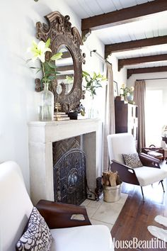 """An 18th-century limestone mantel from Cavendish Grey is the focal point of the living room, here Barrett mixes period furniture — a pair of 1950s Italian loungers, a midcentury coffee table — with a skirted sofa of her own design. """"All the silhouettes complement one another because they're all rounded,"""" she says.   - HouseBeautiful.com"""