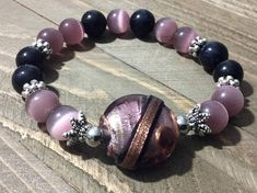 Simple sophistication and style. Be your own beautiful with this stretch bracelet which is made with amethyst cats eye 10mm beads, black onyx 10mm beads, multicolor glass focal bead, silver plated bumpy rondel 8mm, silver plated small beads, silver plated caps, and stretch cord.