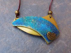 This pendant was created using my latest technique. The pendant is composed of two parts. These were created separately, but were consequently attached into a single item. The colored surface is textured for an organic and striking effect. The other part imitates old and distressed