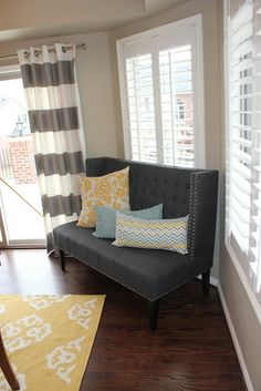 Beige walls, colorful rug and pillows, gray furniture/curtains.