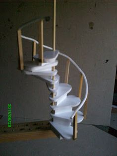 building a spiral staircase step by step - this one is made from foam core board but it could be made of balsa or other this wood.  - site translated from Spanish but pics are easy to follow