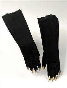 Gants du soir, veau-velours, application de faux ongles en métal doré, couture sellier, couture piquée, Elsa Schiaparelli, 1936. Evoquent la photographie des mains peintes par Picasso, prise par Man Rayu en 1935.