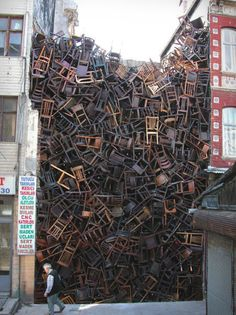 "http://www.mymodernmet.com - ""1550 Chairs Stacked Between Two City Buildings"" is an installation by Doris Salcedo at Istanbul Biennial. In 2002, Salcedo placed 280 chairs at the Palace of Justice in Bogotá ""to pay homage to those killed here in a failed guerrilla coup seventeen years earlier."" In 2003, she filled the Istanbul Biennial space between two buildings with 1,550 chairs ""evoking the masses of faceless migrants who underpin our globalised economy."""