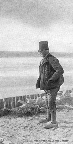 A Dutch man stands by the seashore looking out to sea.  Note the traditional wooden clog shoes that he is wearing.