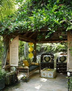 A verdant garden gazebo houses exotic  furnishings. Twin settees are Indian antiques; the pair of African chairs is  intricately carved from a single tree; a low fire pit in the center showcases  French tiles.
