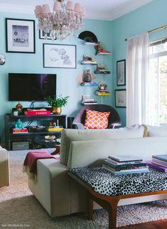 Sala de estar com lustre vintage, banco estampado e pequenas prateleiras para expor livros e objetos.