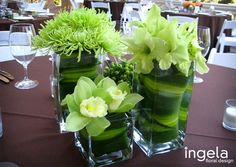 Love...Green center pieces using big leaves wrapped around stems in water.