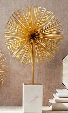 Two's Company Starburst Statue: Add a retro-luxe piece like this one to amp up the wow factor on any coffee table for home or office. A cluster of thin golden rods creates a vibrant decorative explosion, mounted on white marble.12 x 22 $154