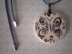 Mandala de cerâmica pintada à mão, esmaltada e queimada.  Colar com aprox. 48 cm de comprimento. Mandala: 5 x 5 cm de diâmetro O fio é de couro ecológio (camurça) na cor azul, com finalizadores prata. A peça é fixada com jacaré em tom de ouro velho. O tamanho pode ser ajustado.   Faça já sua encomenda !!  ,