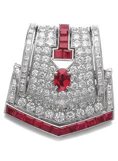 Cartier - An Art Deco ruby and diamond brooch, 1930s. Of ribbon design, pavé-set with circular-cut diamonds, highlighted with an oval and calibré-cut rubies, signed Cartier, partly numbered. #Cartier #ArtDeco #brooch