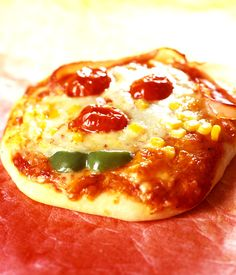 Making smiley faces out of pizza toppings is a a fun activity for young children and gets them eating veggies