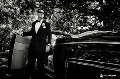 Groom exiting a vintage car on his wedding day.