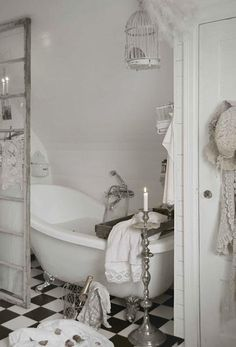 Birdcage and silver candlesticks in bathroom