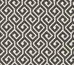 Kyra Key Fabric A woven fabric with an interlocking geometric design in charcoal and ivory.