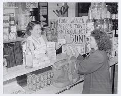 'Rond worden als een ton? Boter, olie en vet v.d. bon!'. Bord op toonbank. Mevrouw Van Meerendonk als klant.
