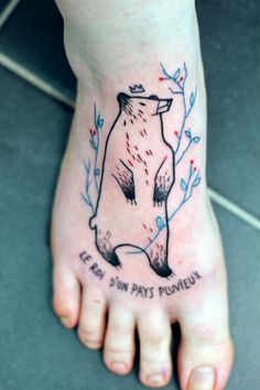 "Bear with a crown and twigs with text tattoo on the foot: ""le roi d'un pays pluvieux"" French, translates to ""The king of a rainy country"" 