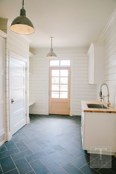 Tiek Built homes| Incredible laundry / mud room with shiplap paneled walls framing a light wood back door with transom window over slate herringbone tiled floors. The cottage laundry room features an open cubby over floating bench across from a stainless steel utility sink with spray faucet illuminated by a pair of galvanized steel dome pendants.