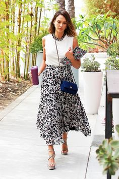 Jessica Alba wears a tank top, thick chain necklace, printed midi skirt, gray platform sandals, and a blue bag