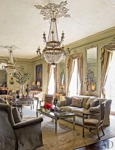 Renovating a French-Inspired Houston MansionLiving Room The ballroom turned living room includes custom-made club chairs covered in a Clarence House velvet, a pair of Empire fauteuils, a mirrored cocktail table by Ellouise Abbott, and a 19th-century writing desk; the carpet is an antique Aubusson.