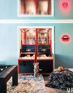 A candy-print Be@rbrick collectible toy stands in front of a Super Shot game machine. Neon light by Studio Job and Seletti. On walls, Benjamin Moore paint.