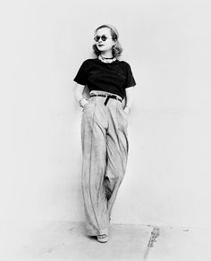 Joan Bennett, c.1938 in wide legged trousers worn with narrow black belt, black top, short necklace and sunglasses