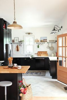 Modern kitchen with black wood cabinets and open shelving. Wood countertops and light chevron floor tiling complete the look.