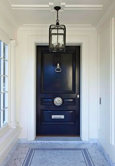 door painted in Benjamin Moore Black Beauty, walls, Monterey White, marble floor, hanging lantern light fixture