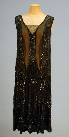 FRENCH BEADED and SEQUINNED CHIFFON FLAPPER DRESS, 1920's. Black chiffon decorated in an allover pattern of black beads and sequins, the V-neck and armholes having gold metallic inserts, scalloped hem. Label: Made in France The House of Adair.