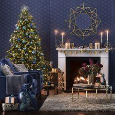 modele de salon bleu indigo décoré de sapin de noel naturel paré de guirlande lumineuse et boules de noel bleues, cheminée blanche et fauteuils bleu marine