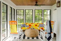 To make natural shades of the lake and lawn of this Minnesota lake cottage pop even more, the owner outfitted the porch in complementary hues of orange and yellow. She covered the futon cushion with an iconic Marimekko print, which inspired the orange-and-yellow paint treatment on the lawn chairs.