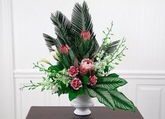 This stunning custom-designed flower arrangement features three long lasting rare protea, with white dendrobium orchids, precious white calla lilies and...