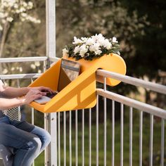 An outdoor flower box balcony shelf from rephorm that doubles as a desk for pleasant days.
