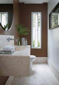 Sintonizado com a natureza, este lavabo é claro e arejado, com uma janela que se abre para o verde do jardim. O tom sobre tom se dá na combinação do branco e marrom das paredes com o mármore travertino do piso e da bancada. Projeto de Tina Ansarah.