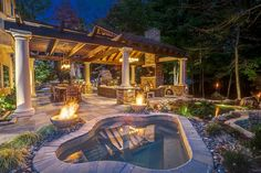 This lovely stone patio features a state-of-the-art spa and an expansive koi pond with waterfall. The space also includes an oudoor dining room and a living room with stone fireplace. An outdoor kitchen features a pizza oven, stainless steel bar and bar seating.