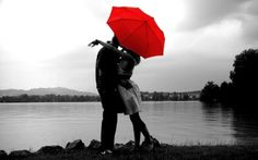 Black and white photograph with a splash of color - a couple, an embrace, a red umbrella.