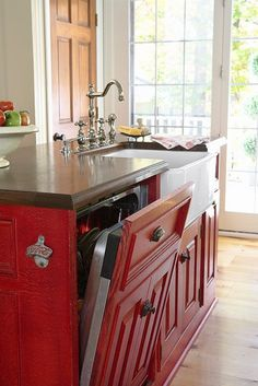 A red cabinet facade with a dishwasher inside. -Traditional Home ®. -  Genius and I love the red!