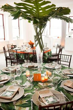 Clusters of orange votive candles surround a tall vase overflowing with bright banana leaves.