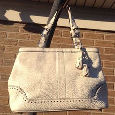 """Cream Leather Coach Bag w/Black Stitching Cream Leather Zip Top Closure Coach Bag w/Black Stitching and Silver Hardware Length-14"""" X Height-8 1/2""""  Depth-4 1/2"""" Strap Drop-8""""-9"""" Signature Tan Interior with 2 multi-function pockets and 1 zip pocket. Exterior Zip Pocket. Beautiful, roomy bag that has been professionally cleaned and conditioned inside and out. Normal wear with some scuffs on exterior, but the interior is excellent and this beauty still has a lot of life left. Coach Bags…"""